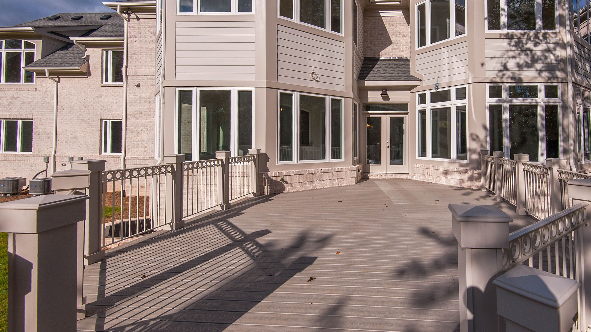 A custom designed composite deck with a beautiful view of the rear year.