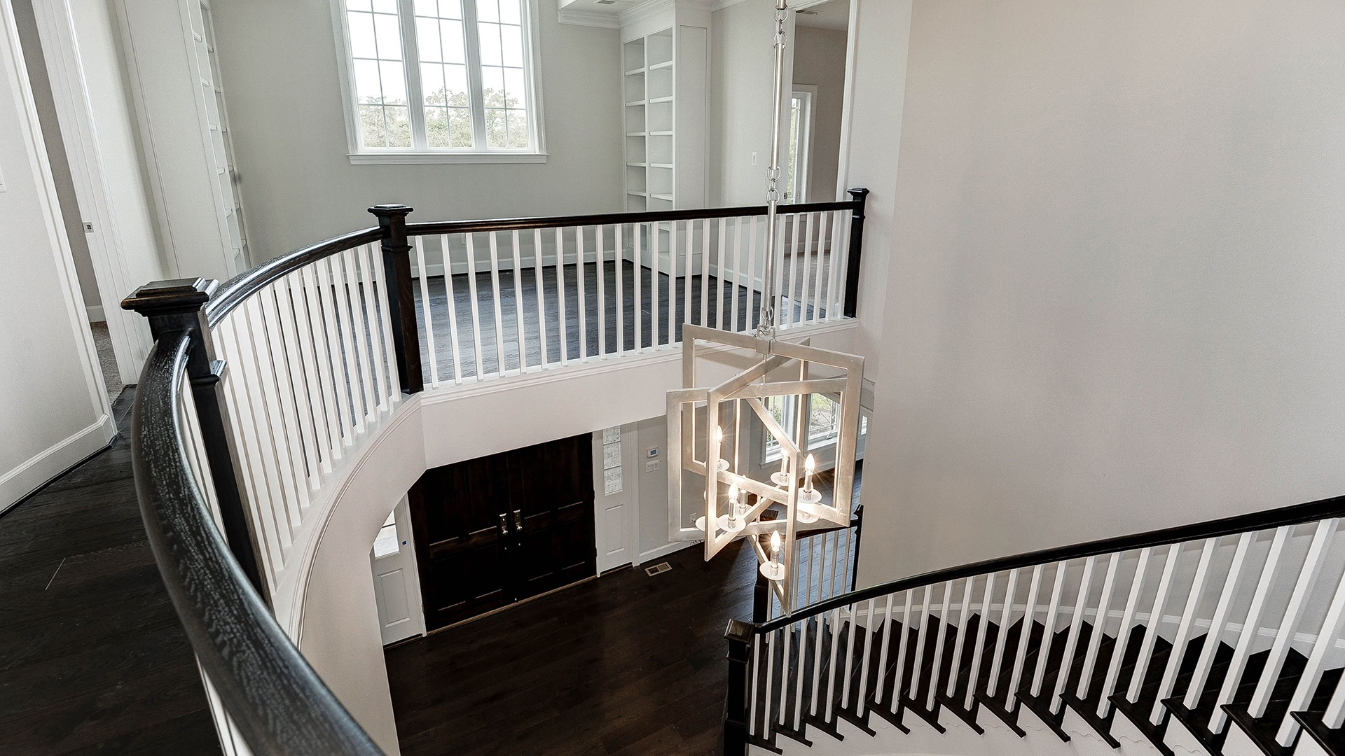 The impressive foyer with dramatic curved stair.