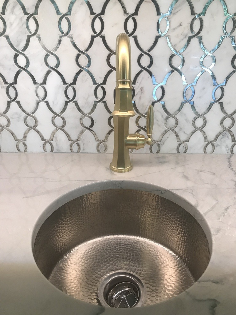 A bar sink with patterned tile.