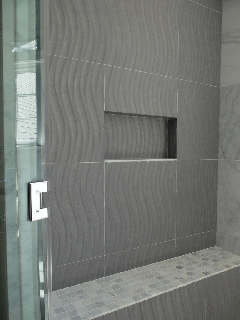 "A shower with ""wave"", patterned tile."