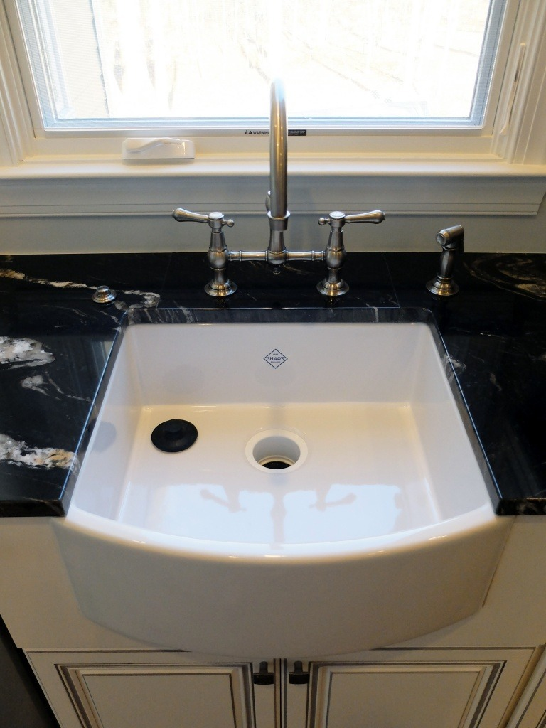 A farmhouse sink with a polished nickel faucet.