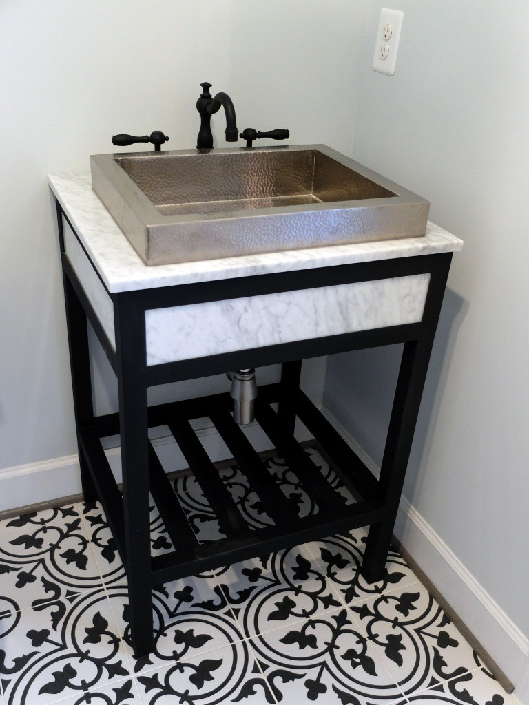 A beaten metal vessel sink with a black faucet.